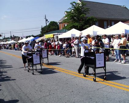3 Librarians rolling book carts down Main Street